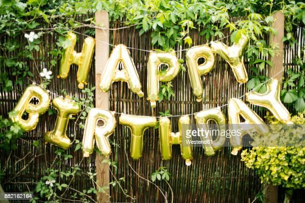 decoration for birthday party in garden with golden balloons - geburtstag stock-fotos und bilder
