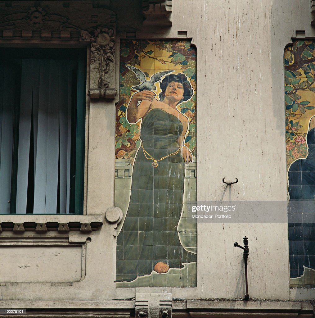 Italy, Lombardy, Milan, Casa Galimberti. Detail of the facade decoration. A dove perches on a woman's hand. She withdraws worried. : Foto di attualità
