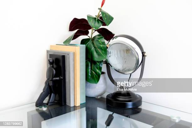 decoration on corner of glass desk with plant, industrial lamp, books and bookend - bookend stock pictures, royalty-free photos & images