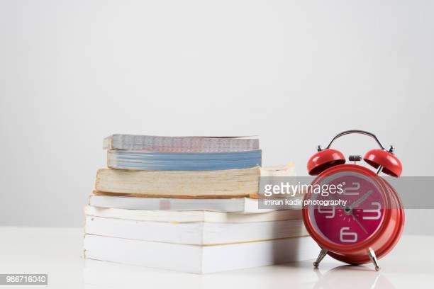 decoration pile of books and clock bell on the white table - time management stock photos and pictures