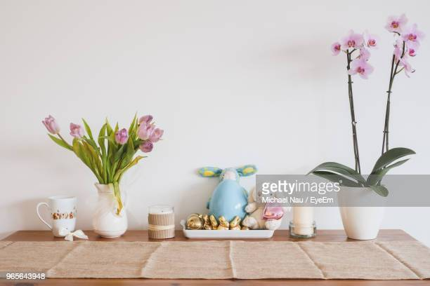 decorations on table by white wall - easter flowers stock pictures, royalty-free photos & images