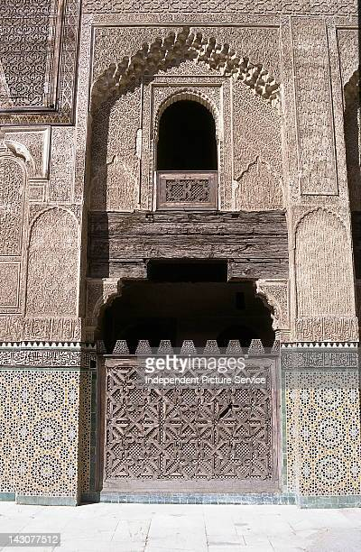 Decorative carved cedar and stucco walls at Bou Inania Medersa Fes Morocco