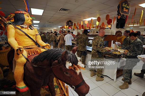 A decorative Native American on horseback centerpiece is seen as US soldiers wait in line for their Thanksgiving Day meal at Bagram air base 50 kms...