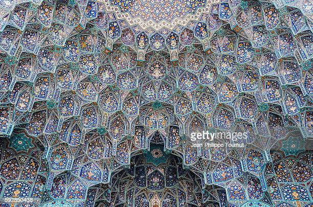 Decorative paintings on the stalactite vaults of the entrance portal of the Shah Mosque in Esfahan, Iran