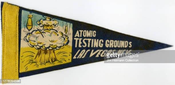 """Decorative pennant shows an comic-style illustration of a mushroom cloud with bombs dropping around it with the title """"Atomic Testing Grounds, Las..."""