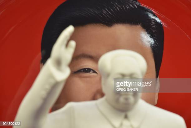 TOPSHOT A decorative plate featuring an image of Chinese President Xi Jinping is seen behind a statue of late communist leader Mao Zedong at a...