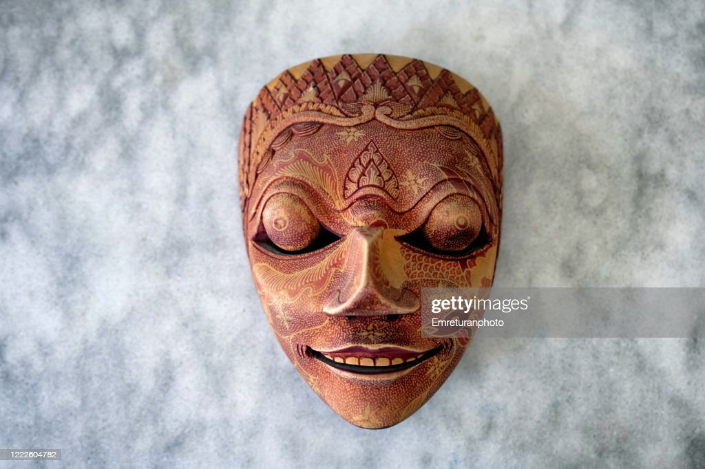 decorative wooden mask from far east on gray marble tabletop : Stock Photo
