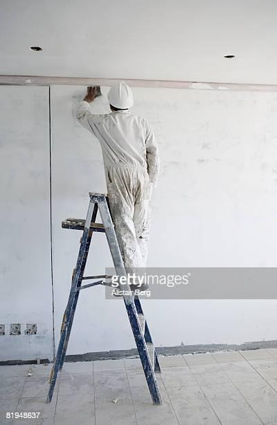 Decorator sanding down wall