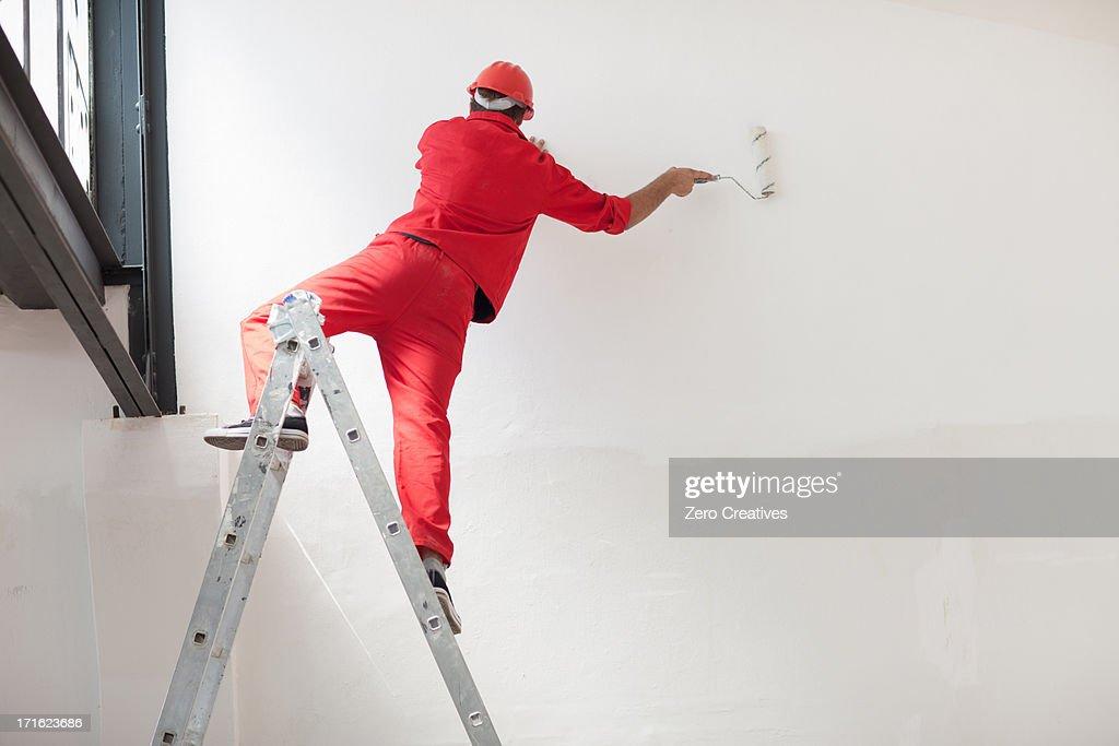 Decorator straddling step ladder : Foto de stock