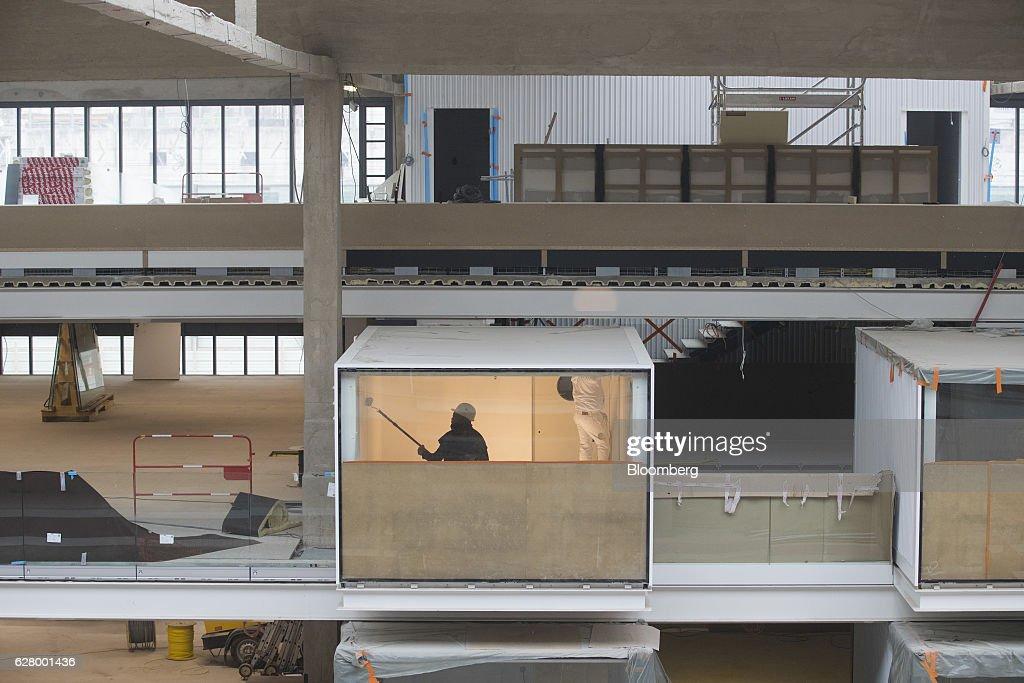 Decorators paint inside a workspace as construction work