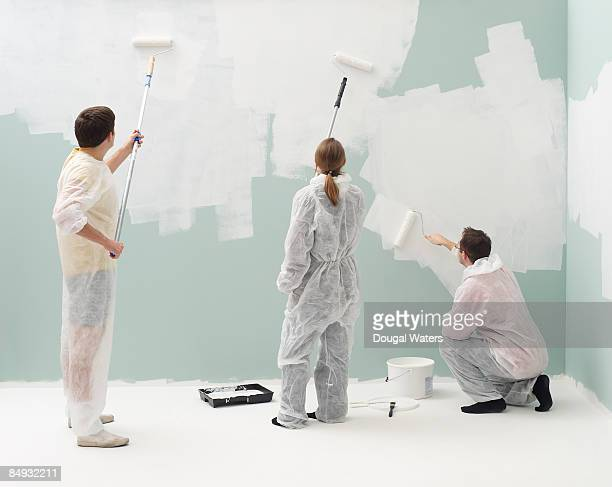 Decorators painting wall.