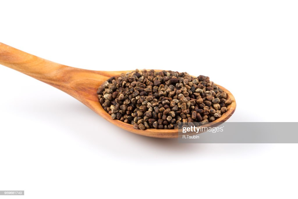 Decorticated cardamom seeds in a wooden spoon on white background : Stock-Foto