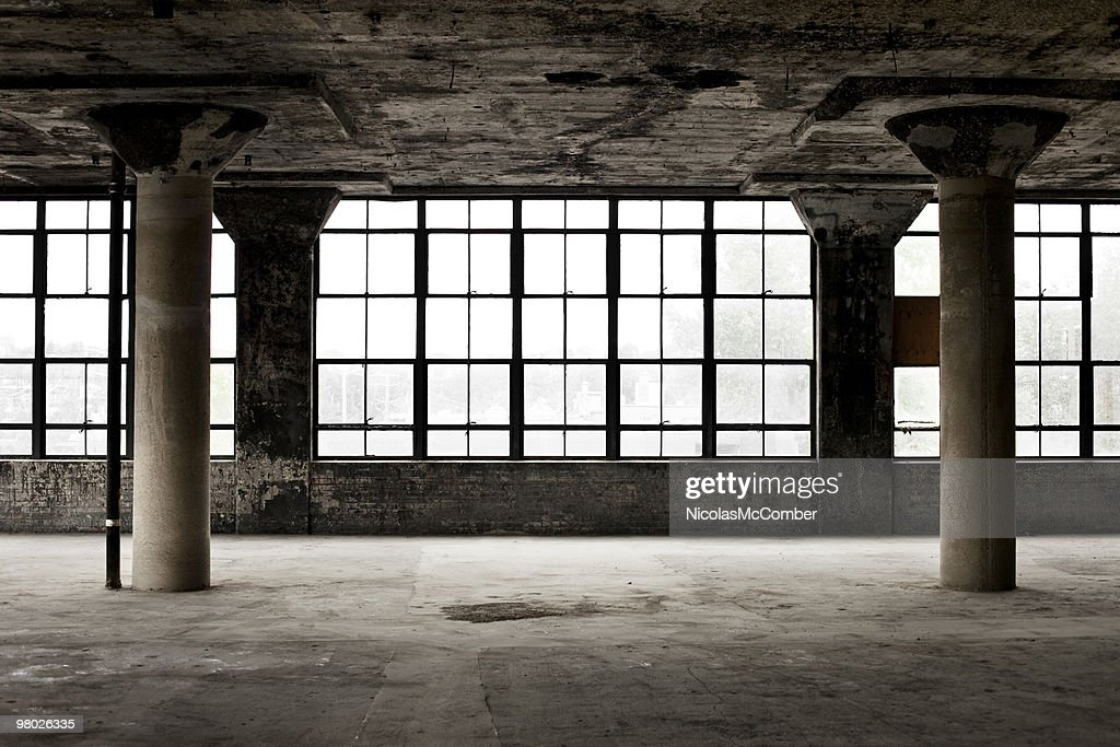 Decrepit industrial loft with columns and windows : Stock Photo