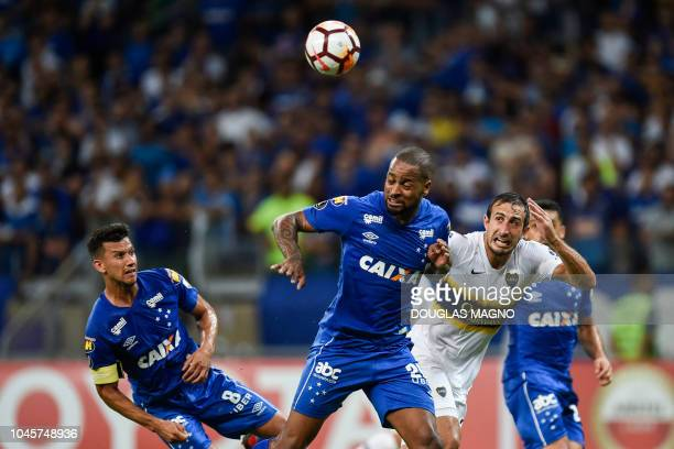 Dede and Henrique of Brazil's Cruzeiro vie for the ball with Agustin Heredia of Argentina's Boca Juniors during their 2018 Copa Libertadores match...