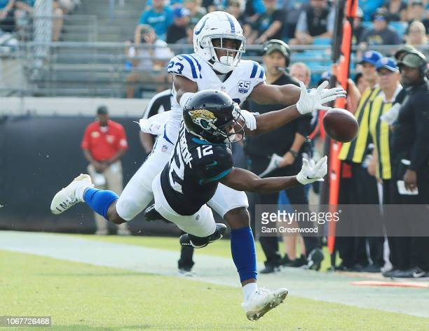Dede Westbrook of the Jacksonville Jaguars and Kenny Moore of the Indianapolis Colts battle for the football during their game at TIAA Bank Field on...