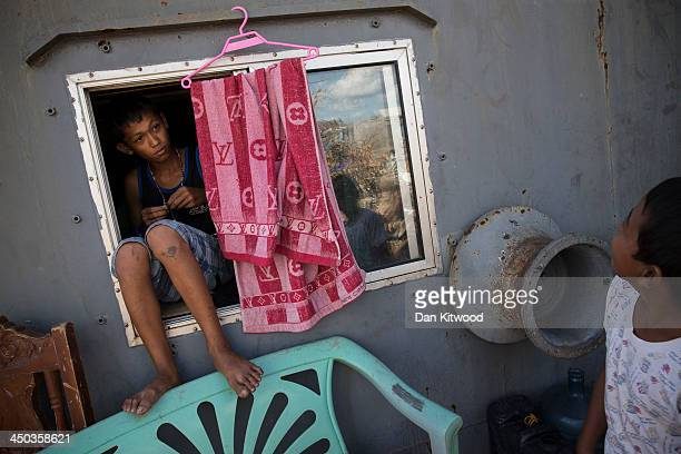Dedenick Omoy 14 leans out of a cabin window aboard a tanker in a particularly badly damaged part of Tacloban on November 18 2013 in Leyte...