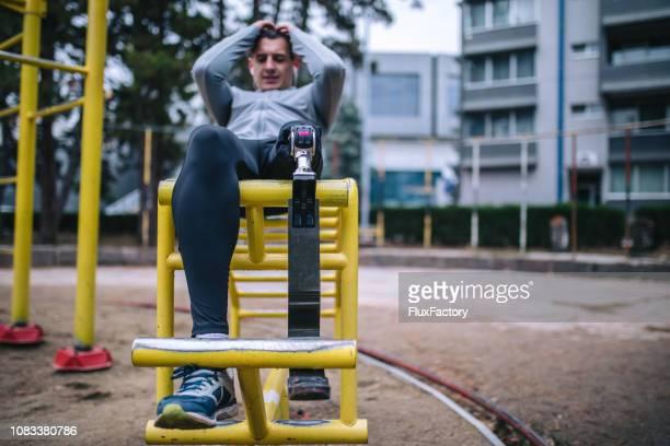 Dedicated adaptive athlete training outdoors doing sit-ups