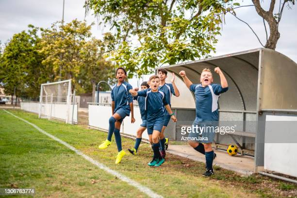 dedicated boy footballers punching the air in support - soccer competition stock pictures, royalty-free photos & images