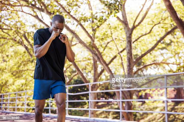 dedicated male athlete jogging in park - one mid adult man only stock pictures, royalty-free photos & images