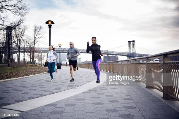 Dedicated multi-ethnic athletes running on footpath with Williamsburg Bridge in background