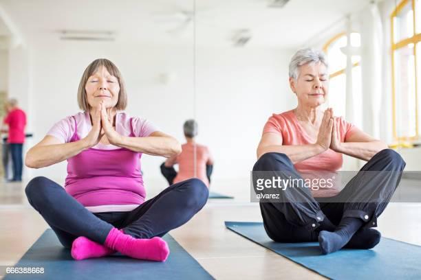 Dedicated senior women meditating in yoga class