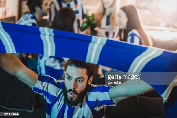 fanático de los deportes dedicado animando a su equipo mientras observa un juego en la televisión en casa. - bufanda fotografías e imágenes de stock