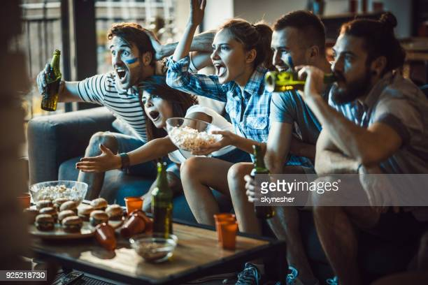 dedicated sports fans watching a game on tv in the living room. - match sportivo foto e immagini stock