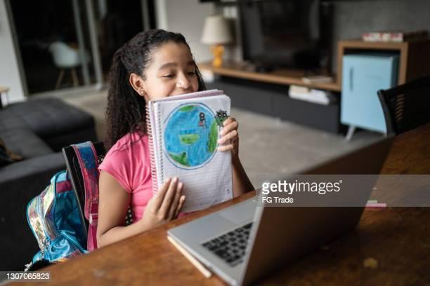 自宅でビデオクラス中に彼女の惑星地球の描画を示す熱心な学生 - 自己改善 ストックフォトと画像