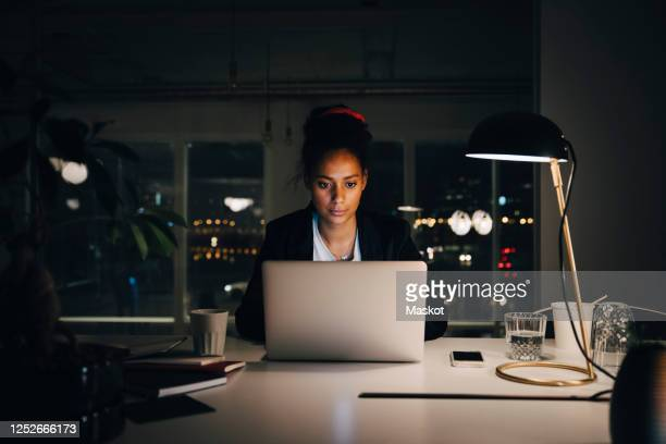 dedicated young businesswoman working late while using laptop at creative office - working late stock pictures, royalty-free photos & images