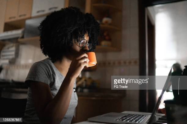 dedicated young woman drinking coffee and reading something on laptop at home - new normal concept stock pictures, royalty-free photos & images