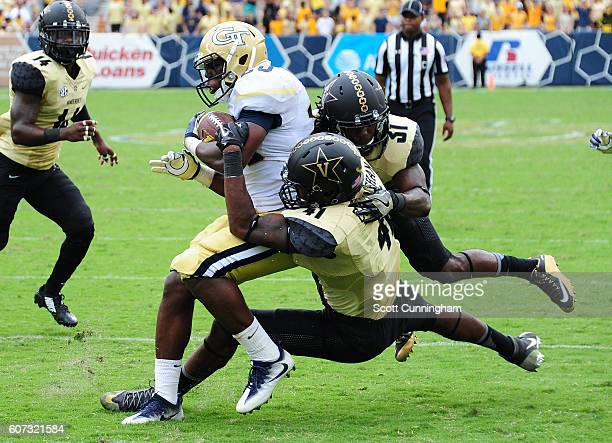 Dedrick Mills of the Georgia Tech Yellow Jackets eludes the tackle attempt by Zach Cunningham and Nate Cotrell of the Vanderbilt Commodores to score...