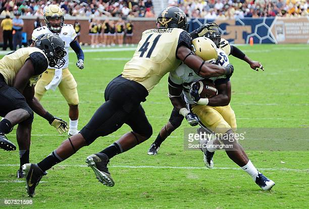 Dedrick Mills of the Georgia Tech Yellow Jackets eludes the tackle attempt by Zach Cunningham of the Vanderbilt Commodores to score a touchdown at...