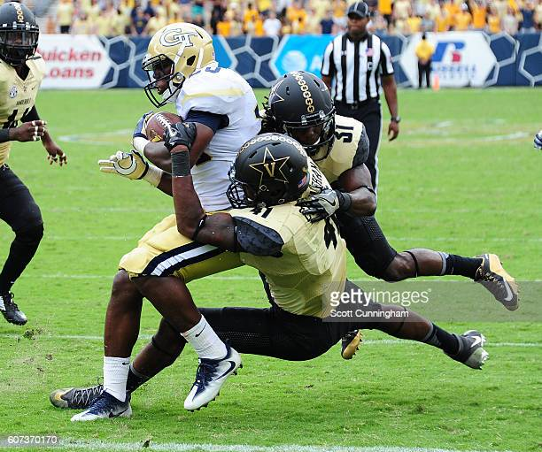 Dedrick Mills of the Georgia Tech Yellow Jackets eludes the tackle attempt by Zach Cunningham and Tre Herndon of the Vanderbilt Commodores to score a...