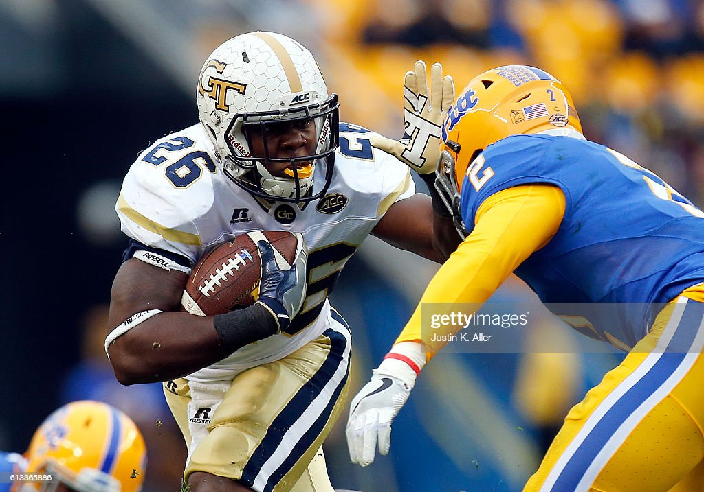 Dedrick Mills #26 of the Georgia Tech Yellow Jackets rushes in the first half during the game against Terrish Webb #2 of the Pittsburgh Panthers on October 8, 2016 at Heinz Field in Pittsburgh, Pennsylvania.