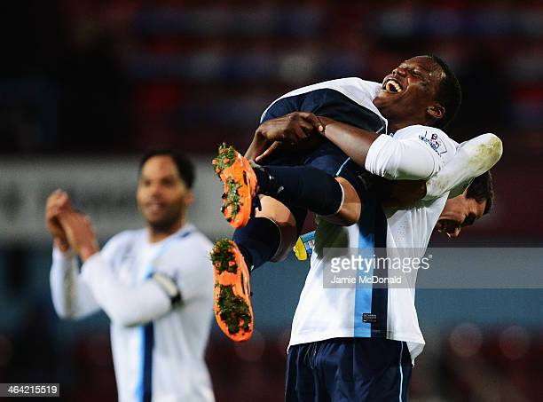 Dedryck Boyata of Manchester City lifts team mate Marcos Mesquita Lopes in celebration after victory in the Capital One Cup SemiFinal Second Leg...