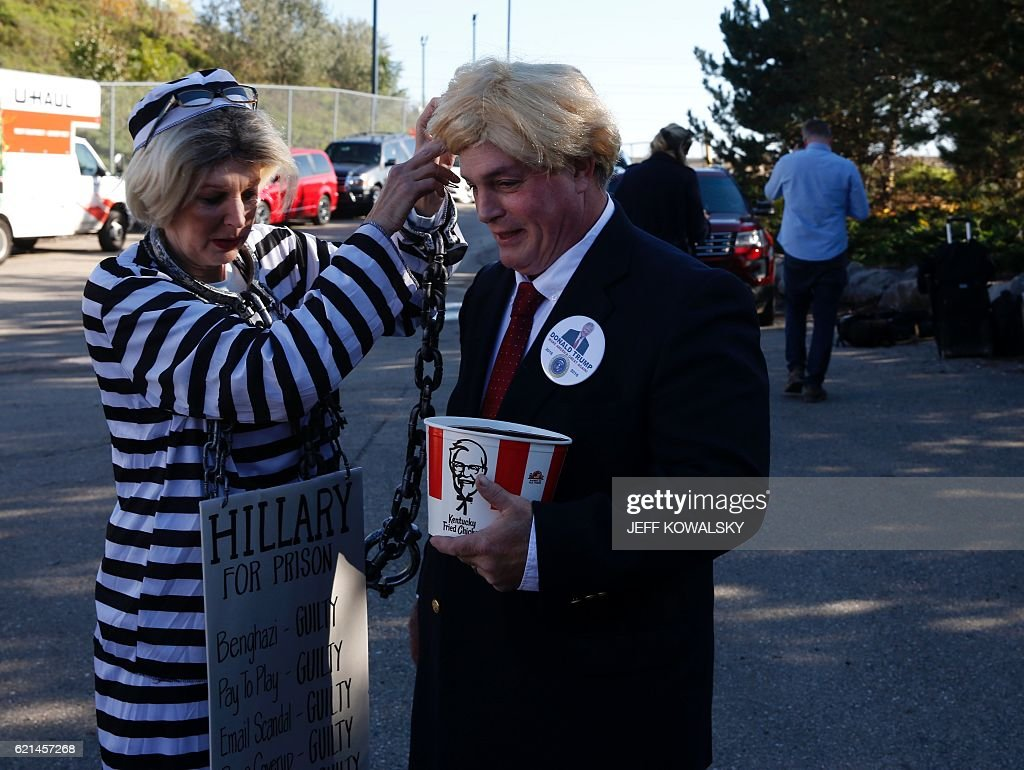 TOPSHOT - Dee(L) and Steve Perry dressed as Hillary Clinton And Donald Trump wait in line to see to see US Republican Presidential nominee Donald Trump address supporters at Freedom Hill Amphitheater on November 6, 2016 in Sterling Heights, Michigan. Donald Trump barnstorms five states Sunday while Hillary Clinton implores her most fervent supporters to get to the polls, in a frenetic final 48-hour dash to the US presidential election. / AFP / JEFF