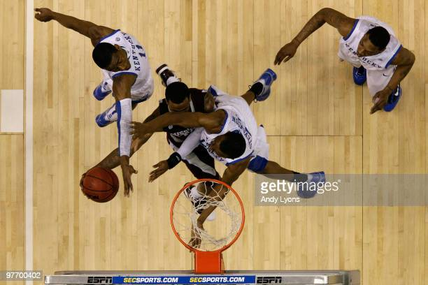 Dee Bost of the Mississippi State Bulldogs draws contact as he drives to the basket for a shot attempt against John Wall, Perry Stevenson and...