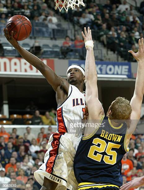 Dee Brown of the Illinois Fighting Illini goes up for two as Graham Brown of the Michigan Wolverines defends during the Big Ten Tournament on March...