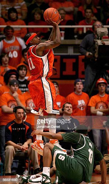 Dee Brown of the Illinois Fighting Illini puts up a shot over Maurice Ager of the Michigan State Spartans on his way to a career high 34 points on...