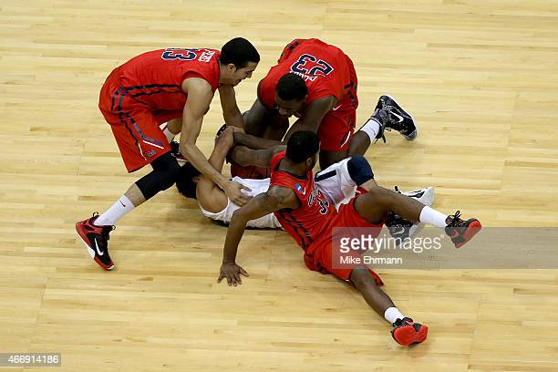 Dee Davis of the Xavier Musketeers is trapped by Anthony Perez Dwight Coleby and Jarvis Summers of the Mississippi Rebels in the first half during...