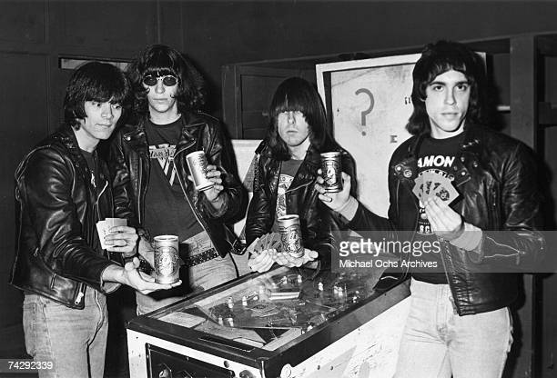 Dee Dee Ramones Joey Ramone Johnny Ramone and Marky Ramone of the rock and roll band The Ramones stand around a pinball table holding Boy Howdy Creem...