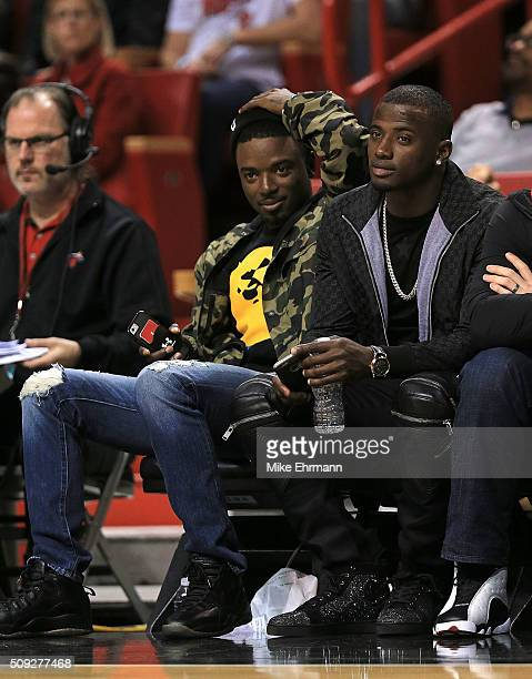Dee Gordon and Adeiny Hechavarria of the Miami Marlins watch during a game between the Miami Heat and the San Antonio Spurs at American Airlines...