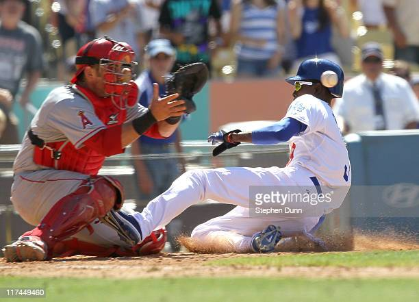 Dee Gordon of the Los Angeles Dodgers beats the throw to catcher Jeff Mathis of the Los Angeles Angels of Anaheim to score the tying run in theninth...