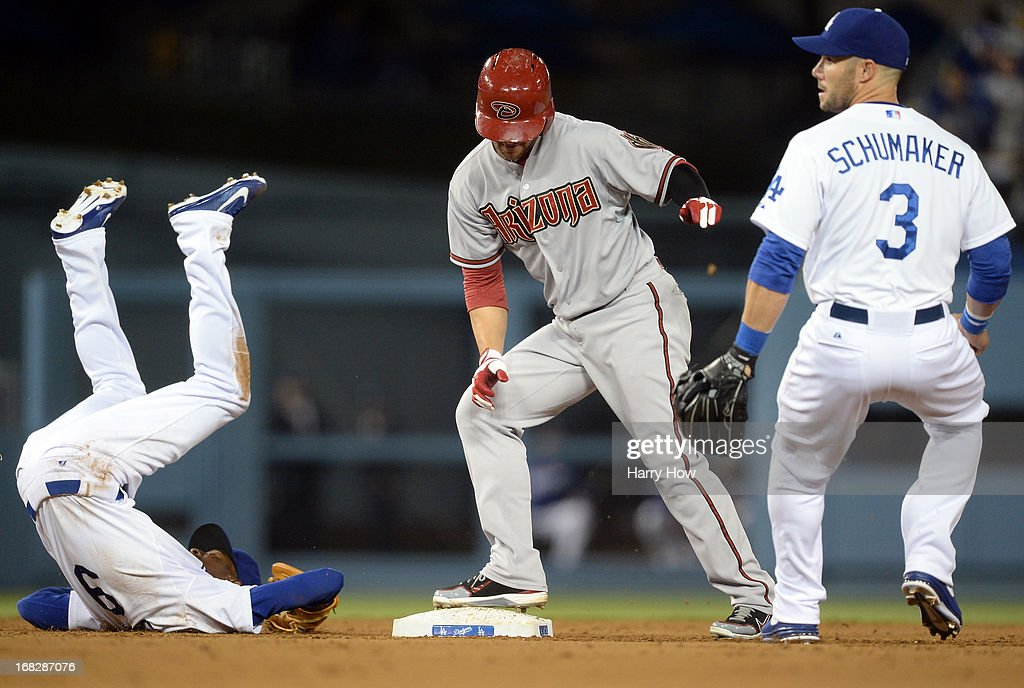 Dee Gordon #9 of the Los Angeles Dodgers flips over after chasing Cody Ross #7 of the Arizona Diamondbacks back to second base as Skip Schumaker #3 looks on during the fourth inning at Dodger Stadium on May 7, 2013 in Los Angeles, California.