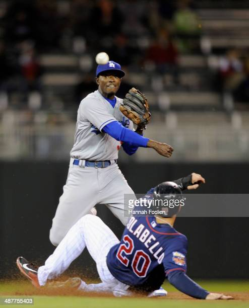 Dee Gordon of the Los Angeles Dodgers gets Chris Colabello of the Minnesota Twins out at second base as Gordon turns a double-play during the sixth...