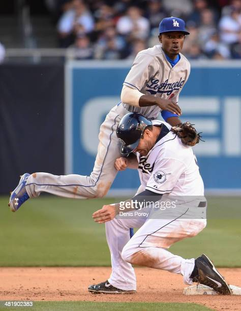 Dee Gordon of the Los Angeles Dodgers goes over Seth Smith of the San Diego Padres as he turns a double play during the sixth inning of a baseball...