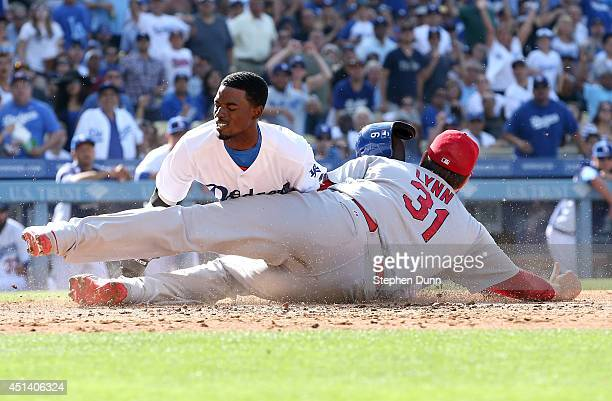 Dee Gordon of the Los Angeles Dodgers is out at home trying to score from second on a wild pitch as he is tagged by pitcher Lance Lynn of the St...
