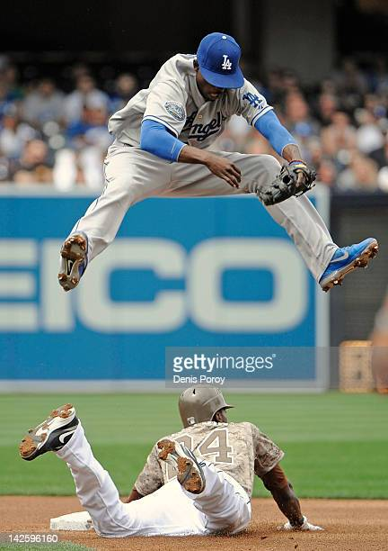 Dee Gordon of the Los Angeles Dodgers jumps over Cameron Maybin of the San Diego Padres as Maybin steals second base during the first inning of a...