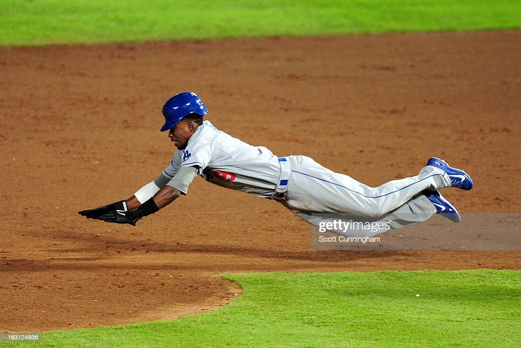 Dee Gordon #9 of the Los Angeles Dodgers slides into second and is caught stealing in the ninth inning against the Atlanta Braves during Game Two of the National League Division Series at Turner Field on October 4, 2013 in Atlanta, Georgia.