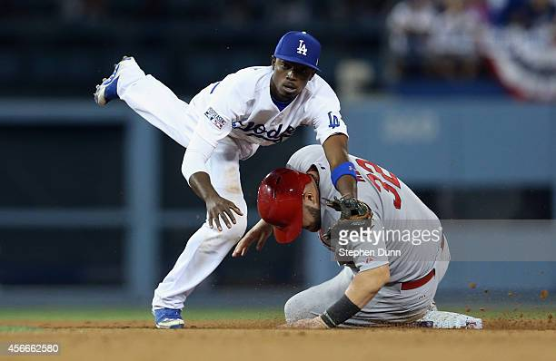 Dee Gordon of the Los Angeles Dodgers turns a double play after forcing out Matt Adams of the St. Louis Cardinals in the eighth inning of Game Two of...
